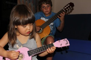 Mia and RJ learning guitar