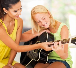 cropped-guitar-teacher-female-bigstock-smiling-beautiful-music-teache-46068454.jpg