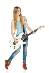 Pretty blond woman playing the guitar in full length over white background